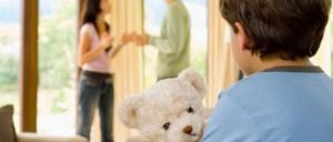 Graphic of divorcing couple in the background with focused foreground of of child holding a teddy bear. John Kinney and Jill Mason of Kinney Mason PC LLO, Attorneys at Law are divorce and family law attorneys with years of experience.